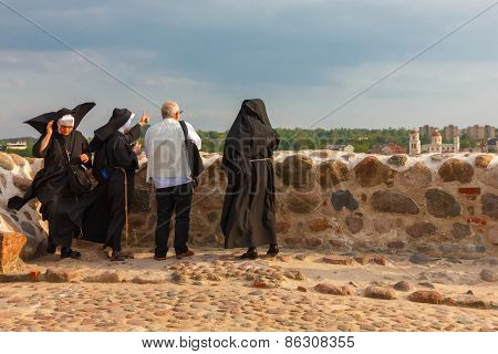 Tourist and three nuns admire the view from Castle Hill in Vilnius, Lithuania