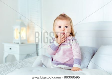 Funny Amazed Blond Little Girl Sitting On Bed In Bedroom