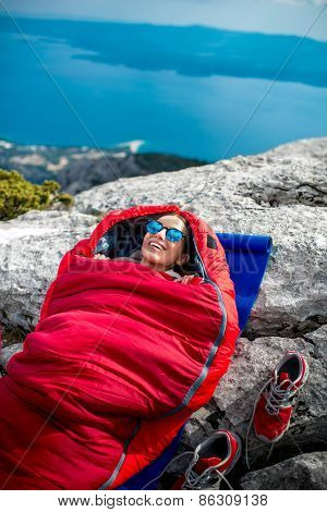Woman in sleeping bag on the mountain
