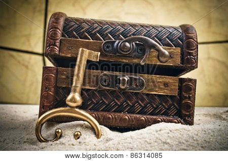Decorative treasure chest with old metal key in the sand