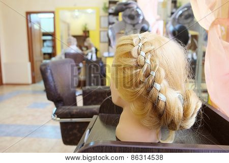 Mannequin's head with hairstyle in hairdresser salon