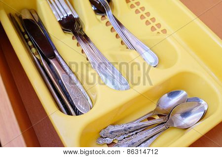 Closeup cutlery in yellow plastic box