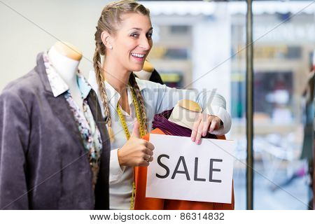 Shopkeeper working at promotion putting sale sign in shop window