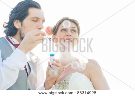 Wedding couple blowing soap bubbles outside