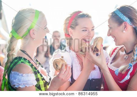 Friends visiting together Bavarian fair in national costume eating grilles sausage in bread roll