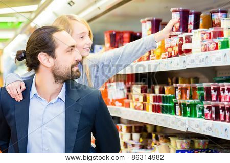 Father carrying daughter on his back while she is selecting dessert at grocery shopping in supermarket