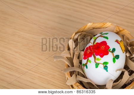 Easter eggs in the nest on wood background