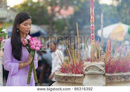 Vietnamese woman praying at temple holding lotus flower buds bunch