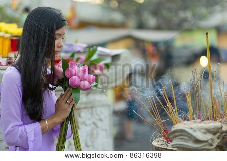 Buddhist Asian woman praying at temple with lotus flower bud bunch