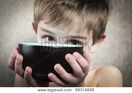 Hunger.   Boy holding an empty bowl.
