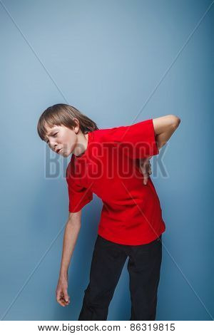 teenager boy brown European appearance in a red shirt holding hi