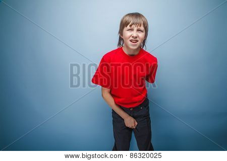 teenager boy in red T-shirt European appearance brown hair holds