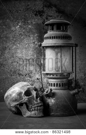 still life with skull human and old hurricane lamp