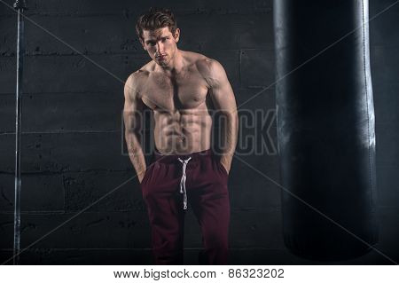 Athletic man with naked torso near concrete wall