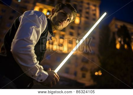 Handsome guy holding a lightsaber Jedi