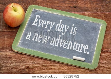 Every  day is a new adventure - positive words on a slate blackboard against red barn wood