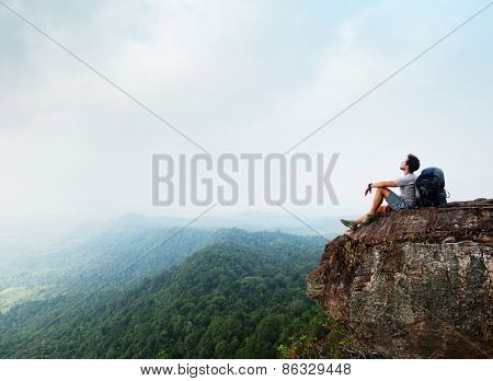 Hiker with backpack sitting on top of the mountain