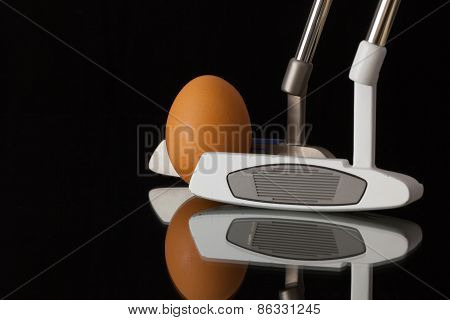 Two Different Golf Putters And Egg