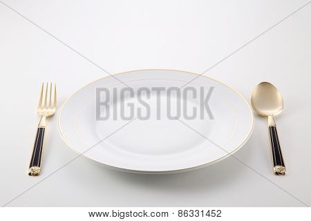 empty plate with golden fork and spoon by the side