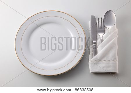 Folded napkin with fork, spoon and knife by the plate