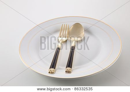 empty plate with golden fork and spoon