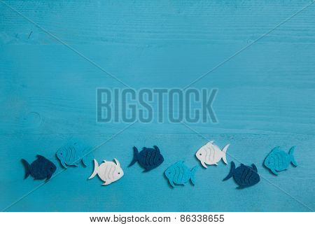 Wooden blue and turquoise background with fishes in a group.