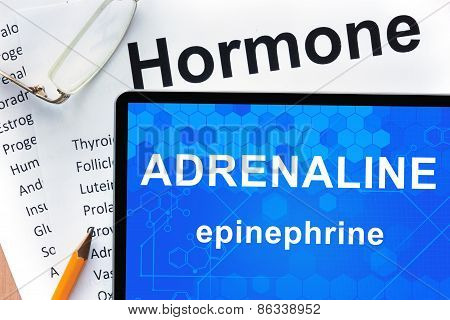Papers with hormones list and tablet  with words adrenaline (epinephrine) .