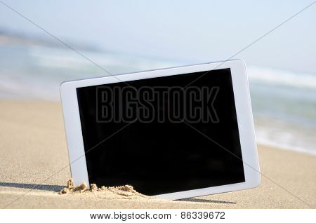 a tablet computer with a black blank space in the screen, in the sand of a beach