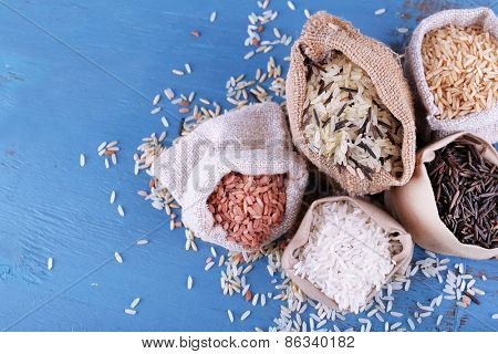 Different types of rice in sacks on wooden background