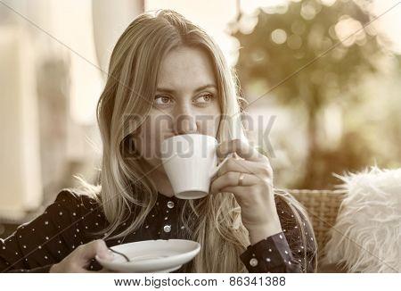Beautiful blonde female drink coffee in cafe