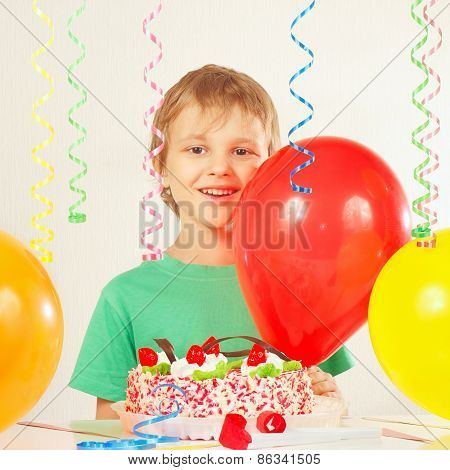 Little kid with birthday cake and balloons