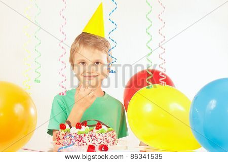 Little kid in holiday hat with festive cake and balloons