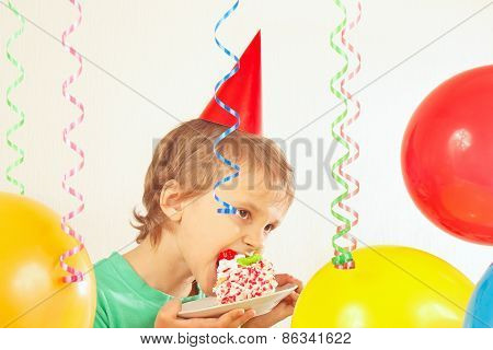 Young boy in festive hat eating birthday cake