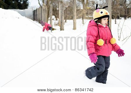 Two Little Twin Girls Are Playing In The Snow. Dressed In Winter Clothes.