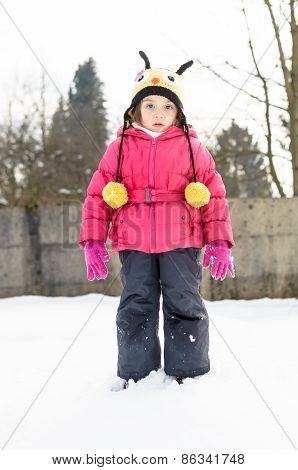 Portait Of A Little Girl In Winter Clothes Having Fun In The Snow