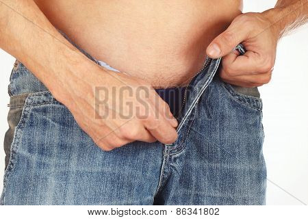 Young men takes off his blue jeans closeup