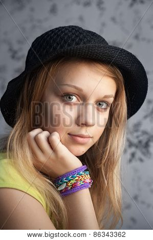Blond Teenage Girl In Black Hat And Rubber Loom Bracelets