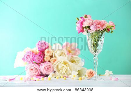 Beautiful spring flowers in glass vase on light blue background