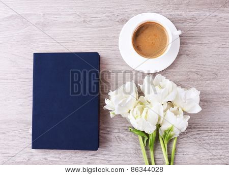 Beautiful tulips with diary and cup of coffee on wooden table, top view