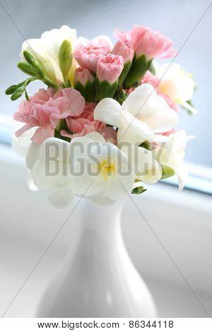 Beautiful spring flowers in vase on windowsill background