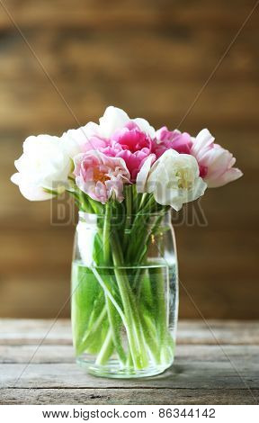 Beautiful tulips in glass vase on wooden background
