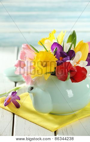 Beautiful spring flowers on wooden table on blue background