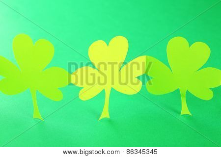 Shamrock leaves on green background