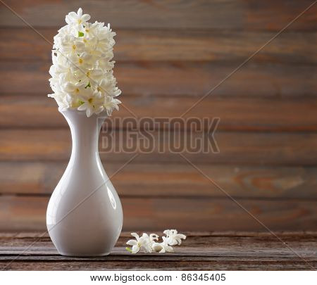 Beautiful white hyacinth flower in vase on table on wooden background