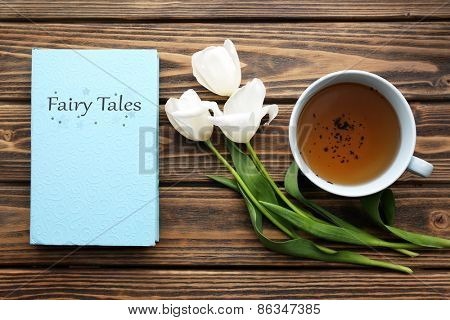 Fairy Tales book with cup of tea and white tulips on wooden background
