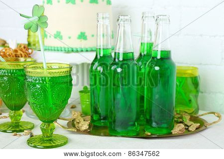 Composition for St Patrick Day with drinks and sweets on table close up