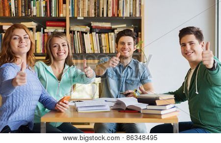 people, education, gesture and school concept - group of happy students with books showing thumbs up and preparing to exam in library