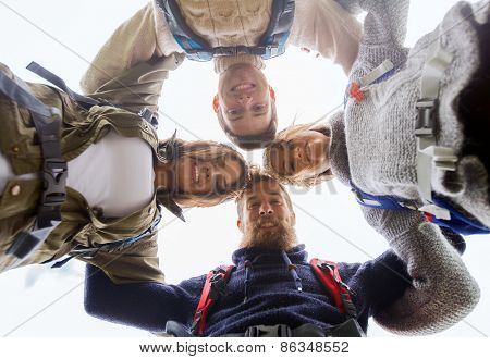 adventure, travel, tourism, hike and people concept - group of smiling friends with backpacks standing in circle and holding to each other outdoors