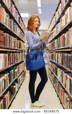 people, knowledge, education and school concept - happy student girl with bag reading book in library