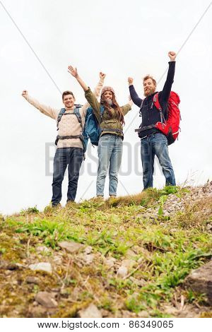 travel, tourism, hike, gesture and people concept - group of smiling friends with backpacks raising hands outdoors